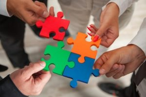 37470361 - group of business people assembling jigsaw puzzle and represent team support and help concept in office.