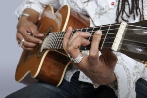 6607939 - close up of a mans fingers holding a chord on the acoustic guitar